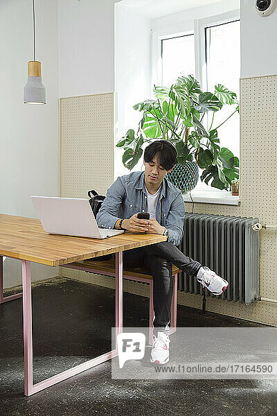 Young man with phone and laptop in co-working space