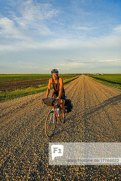 Man cycling through field  Ontario  Canada