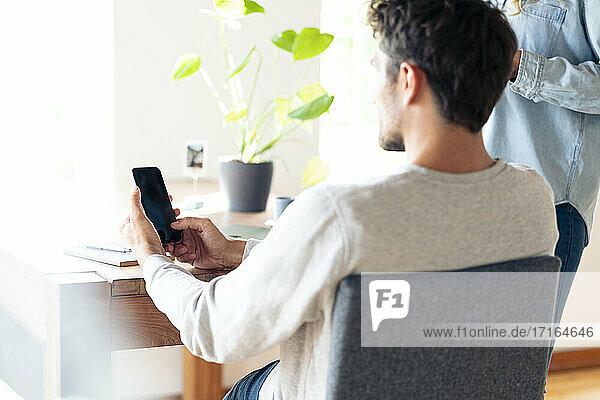 Ein Mann benutzt ein Mobiltelefon  während er am Tisch sitzt und seine Freundin im Hintergrund steht Ein Mann benutzt ein Mobiltelefon, während er am Tisch sitzt und seine Freundin im Hintergrund steht