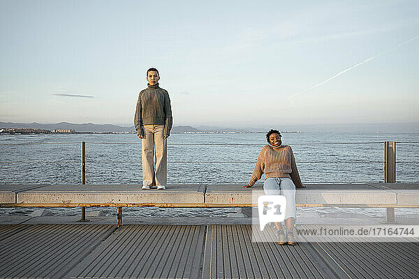 Sad woman standing at distant with happy friend sitting on bench against sea