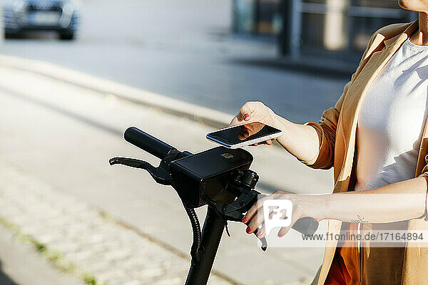Mature female professional using mobile phone for scanning QR code on electric push scooter