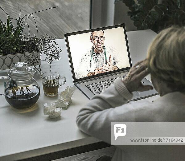 Ältere Frau führt ein Videogespräch mit einem männlichen Arzt über einen Laptop im Wohnzimmer Ältere Frau führt ein Videogespräch mit einem männlichen Arzt über einen Laptop im Wohnzimmer