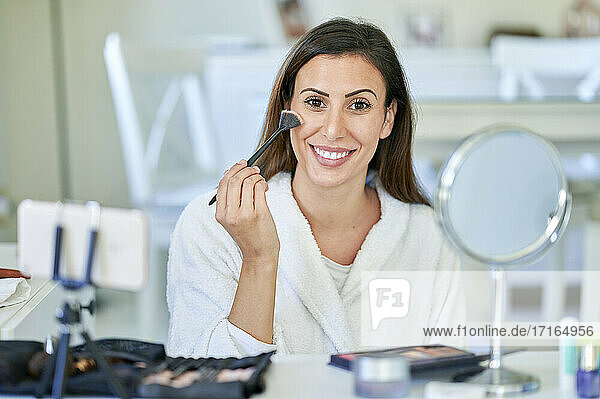 Smiling female influencer vlogging about make-up on mobile phone at home