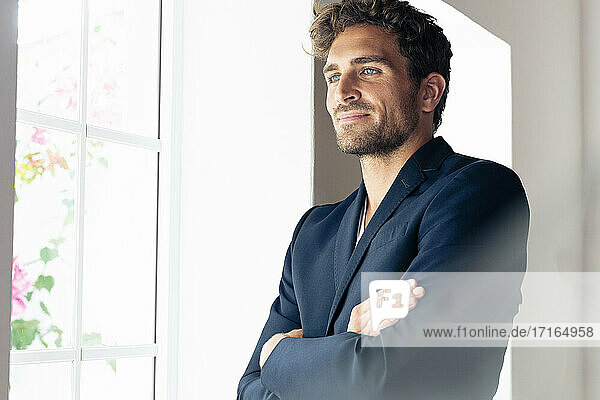 Mid adult businessman with arms crossed looking away while standing by window at home