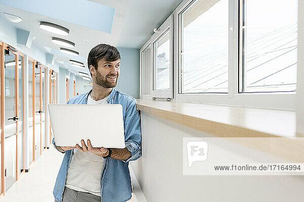 Lächelnder Geschäftsmann  der durch ein Fenster schaut und einen Laptop im Büroflur hält Lächelnder Geschäftsmann, der durch ein Fenster schaut und einen Laptop im Büroflur hält