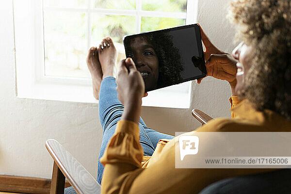 Lächelnde Frau  die ein digitales Tablet benutzt  während sie sich auf einem Sessel zu Hause entspannt Lächelnde Frau, die ein digitales Tablet benutzt, während sie sich auf einem Sessel zu Hause entspannt
