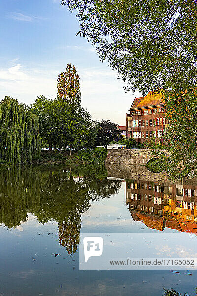Germany  Berlin  Trees reflecting on surface of shiny Weissensee lake