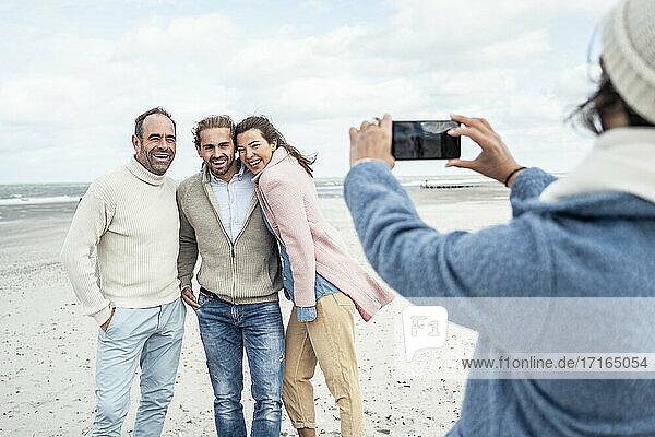 Eine Gruppe von Freunden macht Smartphone-Fotos am Strand Eine Gruppe von Freunden macht Smartphone-Fotos am Strand