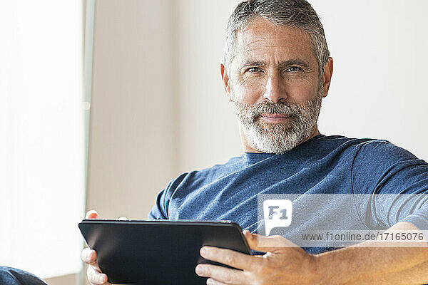 Confident businessman using digital tablet while sitting at home