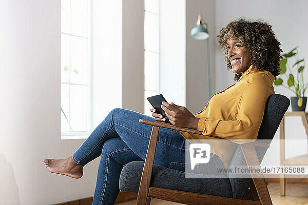 Mid adult woman with digital tablet looking away while sitting on armchair at home