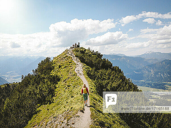 Drone shot of woman hiking on mountain towards peak against sky