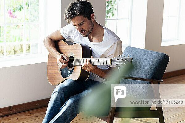 Mann übt auf der Gitarre  während er zu Hause auf einem Sessel sitzt Mann übt auf der Gitarre, während er zu Hause auf einem Sessel sitzt