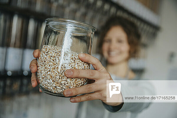Female clerks hands holding jar of food in zero waste store