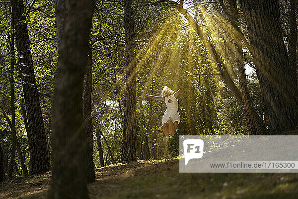 Carefree woman with arms outstretched jumping on land amidst trees in forest