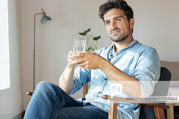 Thoughtful man holding drinking water glass while sitting on armchair at home