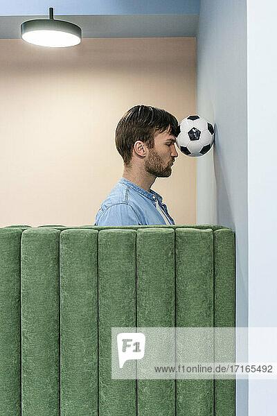 Männlicher Unternehmer drückt Fußball mit dem Kopf an die Wand am Arbeitsplatz Männlicher Unternehmer drückt Fußball mit dem Kopf an die Wand am Arbeitsplatz
