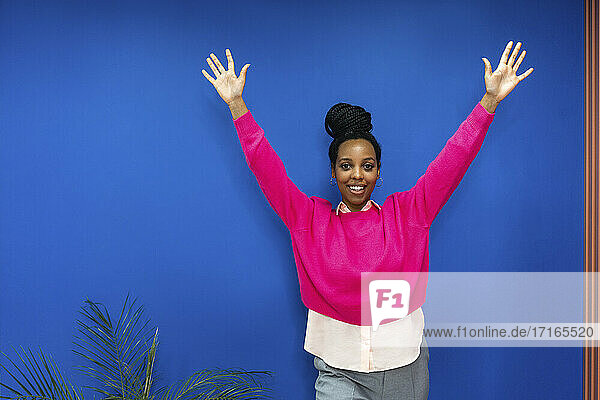 Happy creative businesswoman with arms raised against blue wall at work place