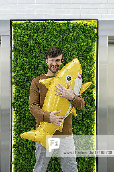 Smiling creative businessman holding inflatable shark against green backdrop