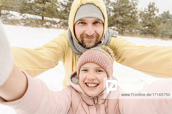 Close-up portrait of smiling father and daughter on snowy landscape