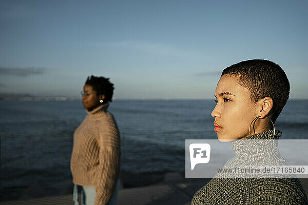 Friends looking away while standing at distance against sea