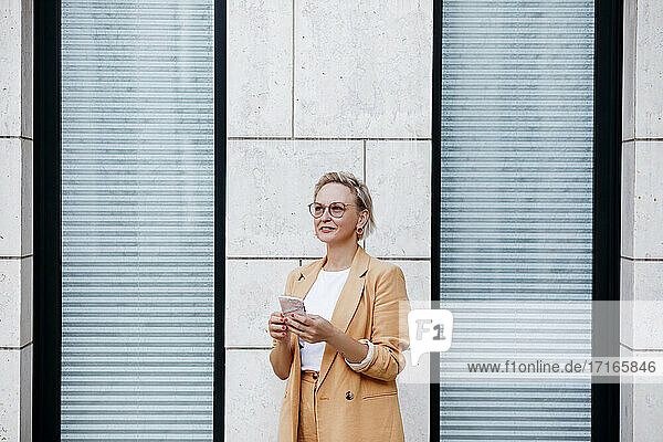 Mature businesswoman with smart phone standing while looking away against wall