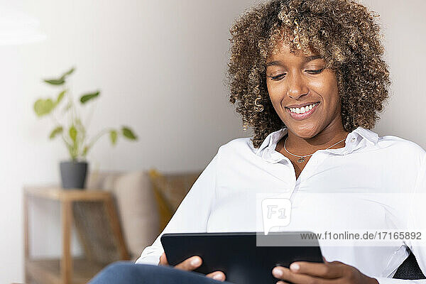 Mid adult woman smiling while using digital tablet sitting at home