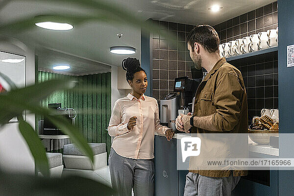 Female professional discussing with male colleague in cafeteria at work place