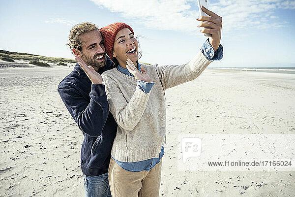 Porträt eines jungen Paares  das zusammen am Strand steht und ein Smartphone benutzt Porträt eines jungen Paares, das zusammen am Strand steht und ein Smartphone benutzt