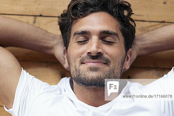 Mann lächelnd beim Entspannen auf dem Boden zu Hause Mann lächelnd beim Entspannen auf dem Boden zu Hause