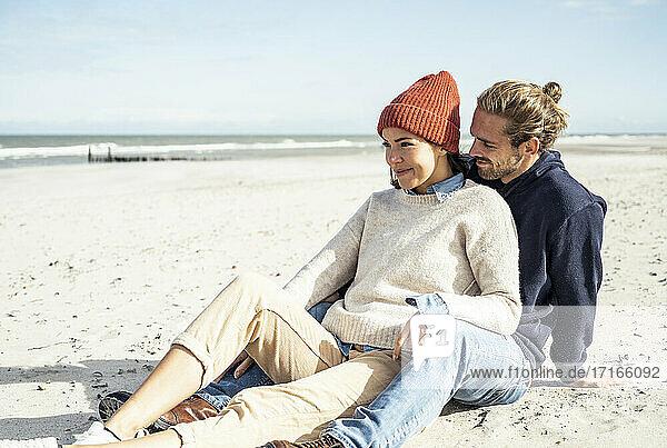 Junges Paar sitzt zusammen am Strand Junges Paar sitzt zusammen am Strand