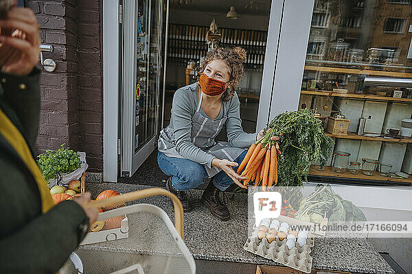 Female owner selling bunch of carrots to customer at store during pandemic