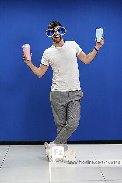 Happy businessman in unicorn slippers wearing novelty glasses while holding coffee cups against blue wall at work place