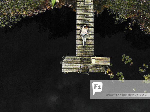 Aerial view of mature woman sitting on pier over lake in forest