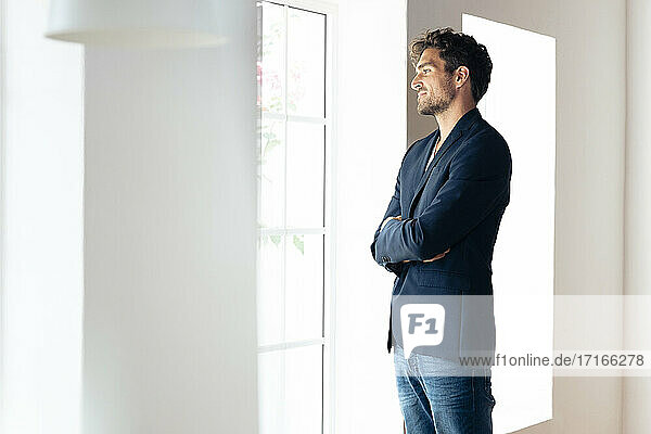 Smiling businessman looking through window while standing with arms crossed at home