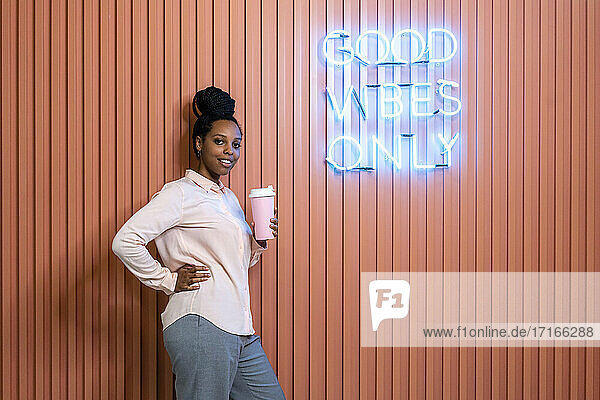 Smiling female professional with hand on hip holding reusable coffee cup by brown wall in office