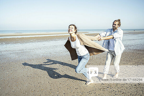 Young man holding hands of girlfriend while running on sand at beach