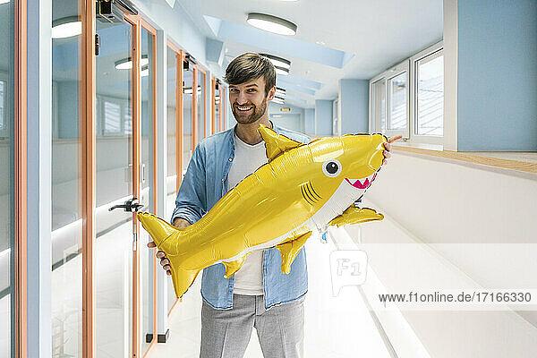 Glücklicher kreativer männlicher Fachmann  der einen aufblasbaren Hai hält  während er im Korridor im Büro steht Glücklicher kreativer männlicher Fachmann, der einen aufblasbaren Hai hält, während er im Korridor im Büro steht