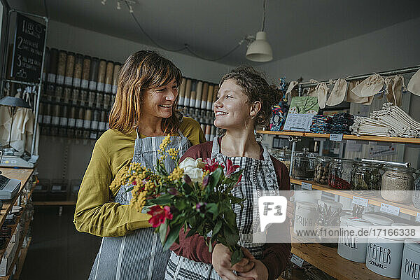 Female colleagues holding flowers while looking at each other in retail shop