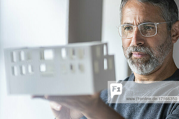 Businessman wearing eyeglasses examining architectural model while standing at home
