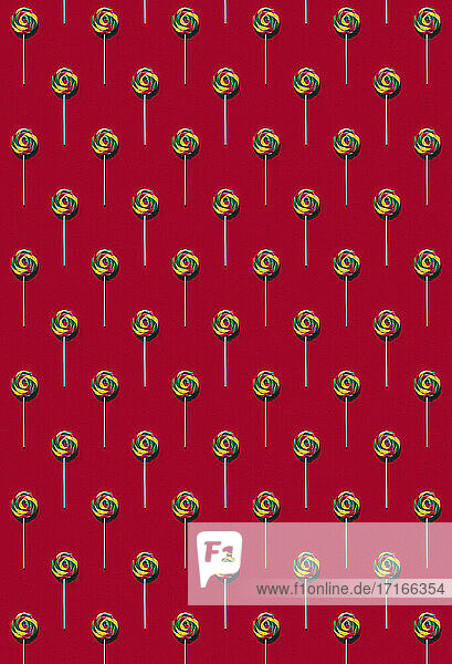 Pattern of multi colored lollipops against red background