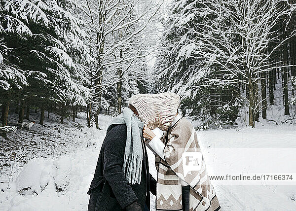 Romantic couple covering face with scarf while standing on snow in forest