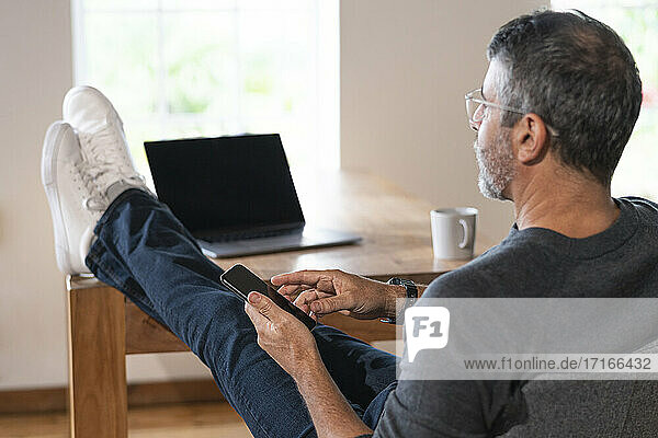 Businessman using mobile phone while sitting at home office