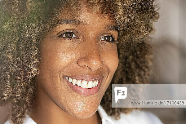 Close-up of curly hair woman smiling while looking away at home