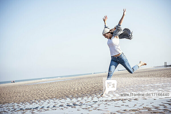 Cheerful young woman with arms raised jumping over wet sand at beach