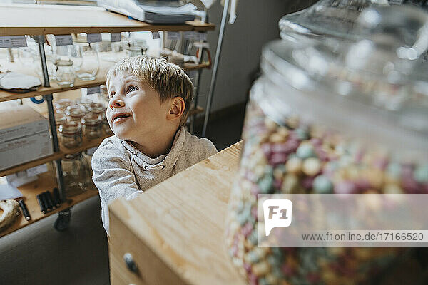 Blond little boy day dreaming while standing in candy store