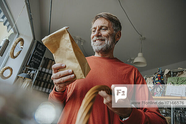 Happy mature man looking at brown package while standing in retail store