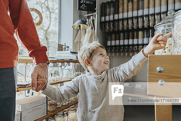 Cheerful boy holding hand of father while pointing at candy jar in store
