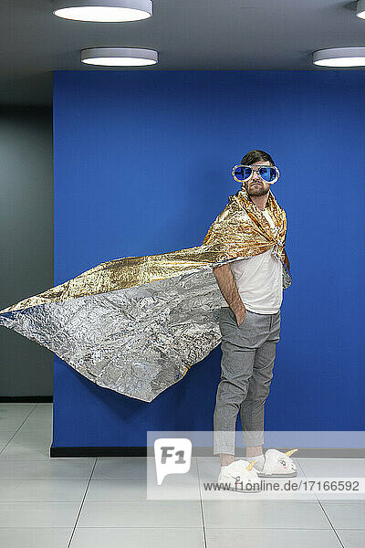 Businessman in gold color wrapping paper cape looking away by blue wall at workplace