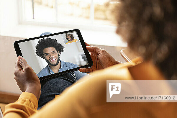 Woman talking with smiling man on video call through digital tablet while sitting at home