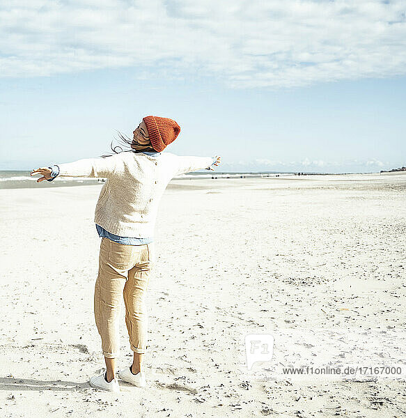 Young woman standing on sandy beach with raised arms